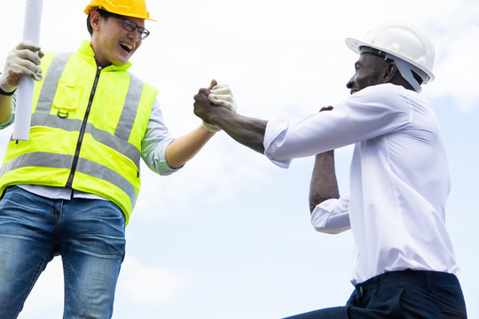 Architect and engineer construction worker shaking hands on construction site.