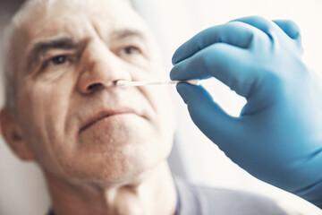 Medical worker wearing protective equipment testing senior old man for dangerous corona virus using test swab stick