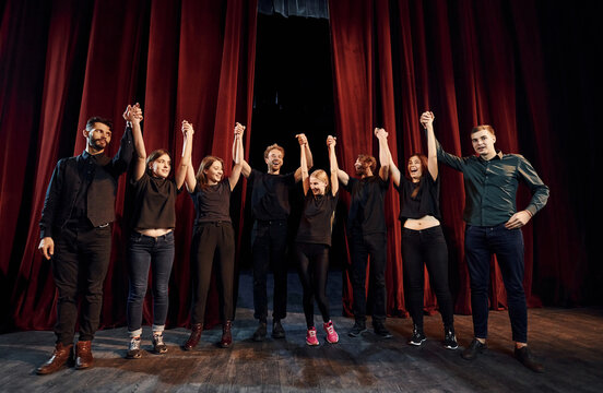 People bowing to audience. Group of actors in dark colored clothes on rehearsal in the theater