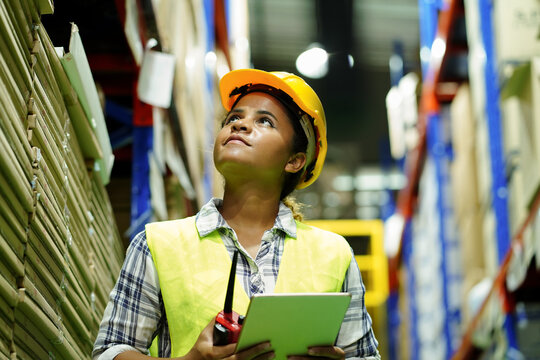 Warehouse worker wear safety equipment inspect and check goods package shelf in storage for supply import export logistic