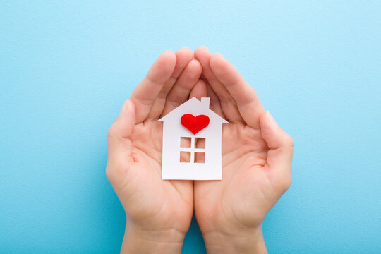 White paper house with bright red heart in young adult woman palms on light blue table background. Pastel color. Closeup. Point of view shot. Top down view.
