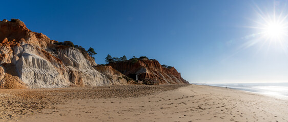 panorama view of a wide empty golden sand beach with colorful sand cliffs on a sunny day