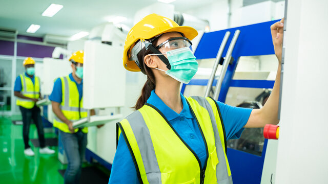 Portrait of Pretty technician or worker or engineer woman with hygienic mask stand with confident action in workplace during concern about covid 2019 pandemic in people affect industrial business.