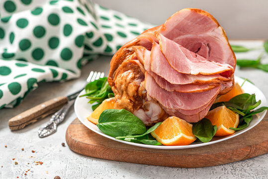 Sliced ham in a plate close-up. Baked pork ham with oranges and spinach on a gray concrete background.