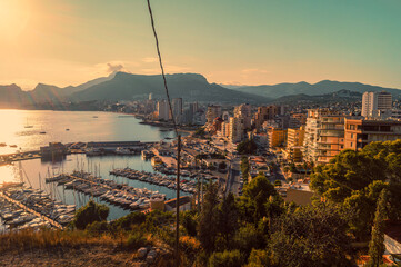 Beautiful sunset with views of the marina and the beach of the city of Calpe from the Peñon de Ifach natural park (Alicante, Spain).