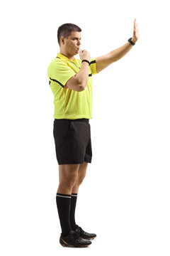 Football referee blowing a whistle and gesturing stop with hand