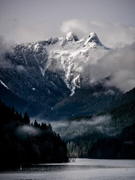 Lions peak mountain in the fog. Clouds and snow from cleveland dam and Capilano Lake