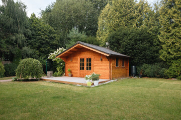 Fototapeta Orange wooden hut in the garden with many tall trees. Garden shed with lawn in front of him obraz
