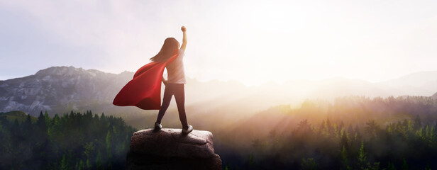 Fototapeta little girl dreaming of being a superhero in a beautiful mountain landscape with a raised fist