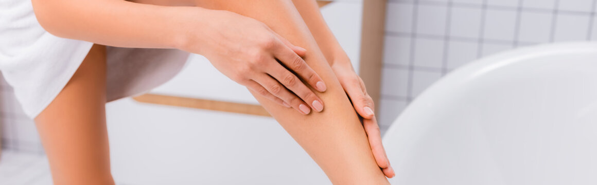 cropped view of woman applying body lotion on leg in bathroom, banner