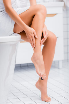partial view of woman applying moisturizing body lotion on leg in bathroom