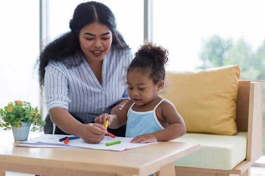 Happy African American mother and her little daughter. Mother teaching her daughter drawing and painting. Mom spending time with her daughter. Happy family at home