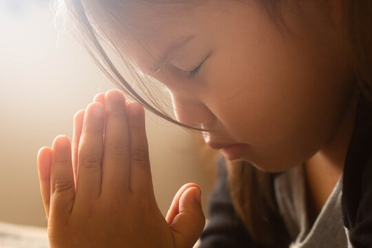 People praying to god. A little girl in prayer with her hands folded, at home.