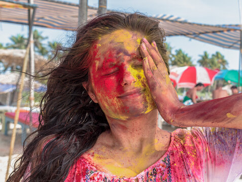 Amazing candid photo of young girl playing and enjoying Holi, festival of colors in India. Applying vibrant shade of colors on her face by hand and closed eyes as she is taken by surprise. - Colorful