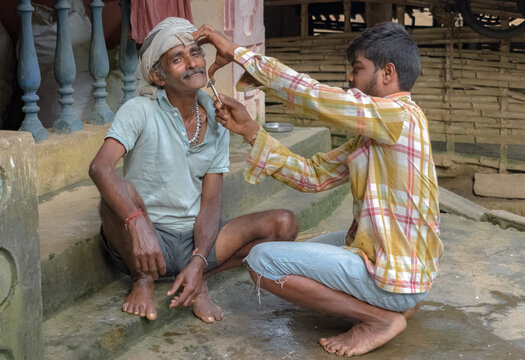 Amazing photo showing father son relationship of love and care. in family. Young Son helping his middle aged father in getting ready by giving salon service at home by grooming his beard. - Image.