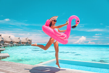 Happy fun luxury hotel vacation woman jumping of joy taking selfie with pink inflatable swimming pool mattress at overwater bungalow resort.