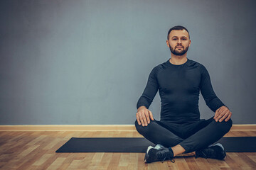 Man sitting at lotus yoga pose. Home morning routine. Teacher fitness studio. Asana class. Online exercise. Relaxation indoor. Male prayer in house room.