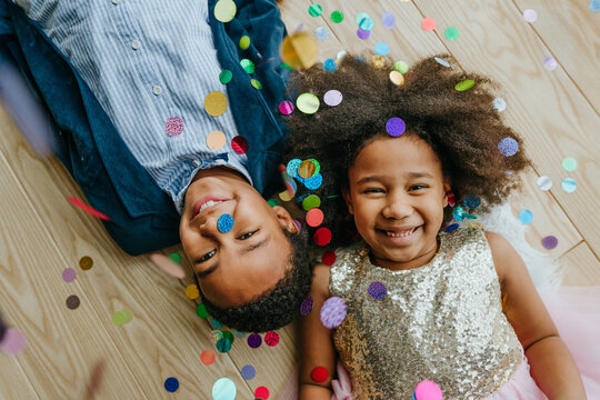 Two happy smiling siblings boy and girl lying on the floor under flying confetti