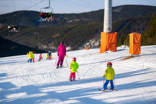 Group of children on the ski slope during the ski school lesson.