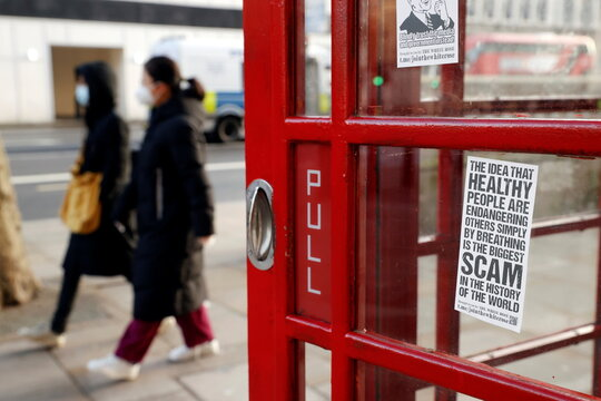 People walk past a telephone booth with an anti-lockdown sticker on it in London
