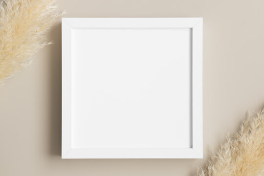 Top view of a white square frame mockup with pampas decoration.