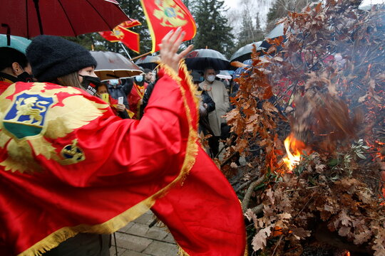 """A girl draped with Montenegro's flag throws dried oak branches """"badnjak"""" on fire in Cetinje"""