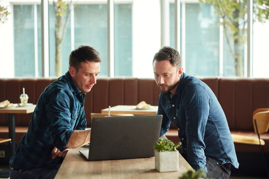 Two men seated in a cafe looking at a laptop screen