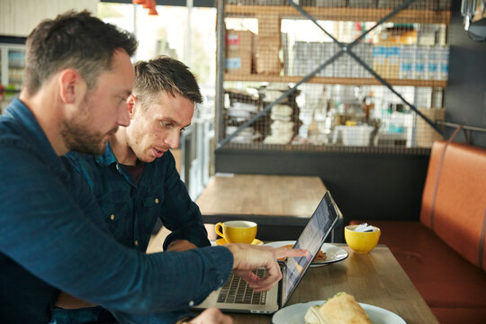 Two men seated in a cafe using a laptop sharing a screen