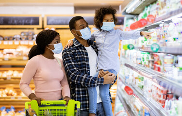 Family shopping during coronavirus pandemic. Black family with child wearing face masks, purchasing food at supermarket