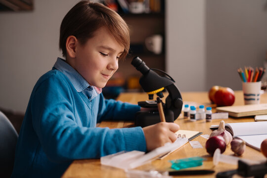 Distance online education, internet learning. First grade boy studying at home using microscope, making notes, biology online lesson