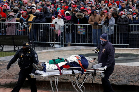 A supporter of U.S. President Donald Trump is carried by paramedics during a rally in Washington