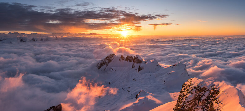 Panoramic shot of mountains covered in snow under a sunrise sky