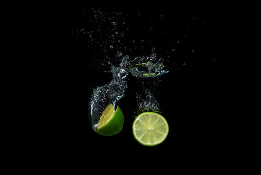 Fresh lime falling into the water isolated on a black background.
