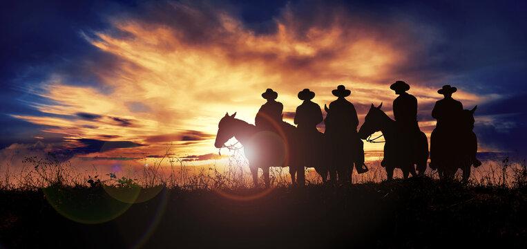Group of cowboys on horseback at sunset
