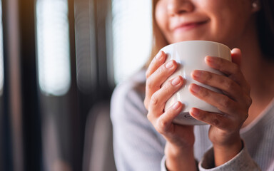Closeup image of a beautiful young asian woman holding and drinking hot coffee in cafe