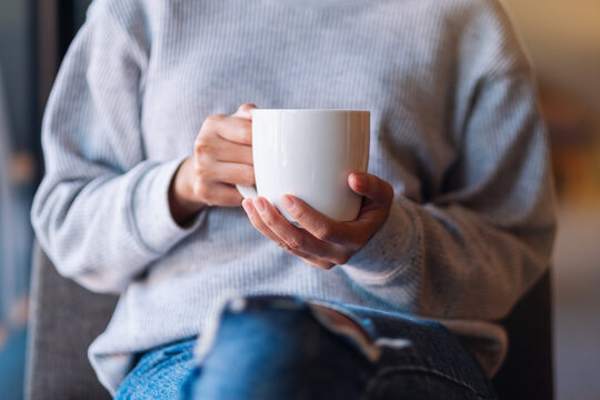 Closeup image of a woman holding a cup of coffee in cafe