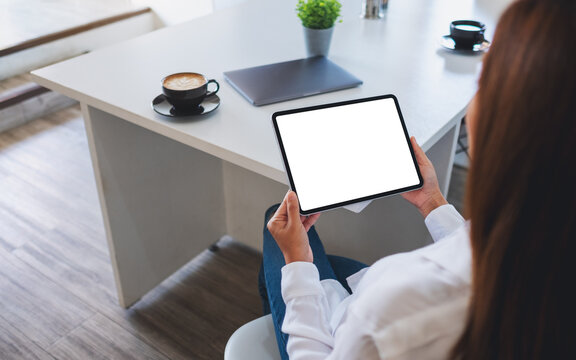 Mockup image of a business woman holding digital tablet with blank white desktop screen