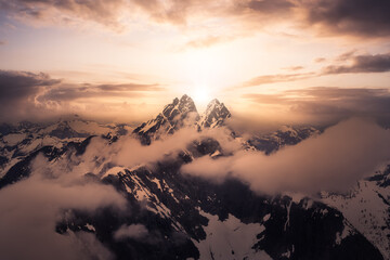 Dramatic Artwork. Aerial landscape view of the snow covered mountain range near Chilliwack and Vancouver, British Columbia, Canada. Artistic Sunset Sky Render
