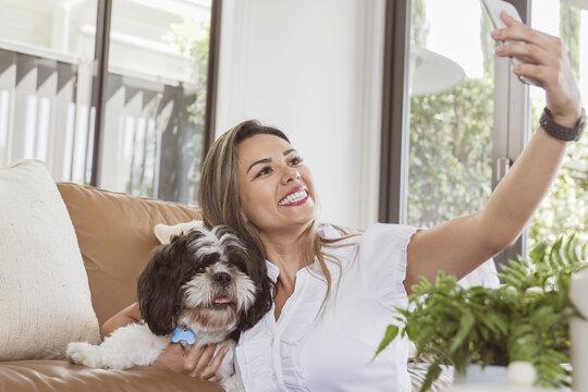 Beautiful Brazilian woman trying to take selfie with her shih tzu pet dog, taking video call at home