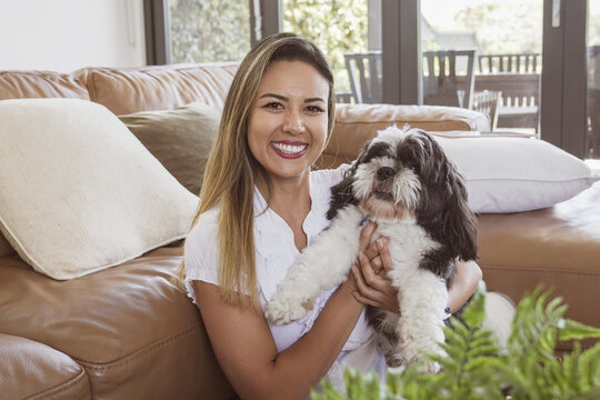 Portrait of beautiful Brazilian woman and her pet shih tzu dog at home, best friend, family love
