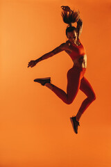 Portrait of fit woman jumping in air during workout