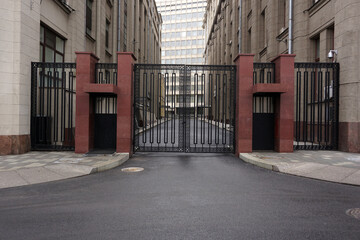 Black metal gates close the transition and passage along the street. Fotobehang