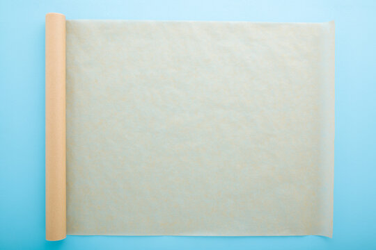 Rolled out roll of baking paper on light blue table background. Pastel color. Closeup. Empty place for text. Top down view.