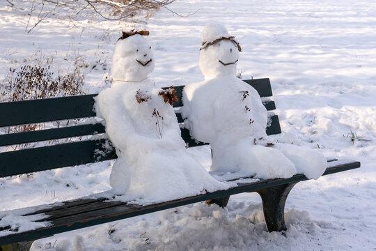 Schneemann und Schneefrau auf einer Parkbank