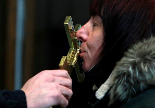A woman kisses a cross during the Orthodox Christmas mass at St Kliment Orthodox in Skopje