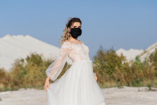 Bride in wedding dress with medical mask at coronavirus covid-19 quarantine period.