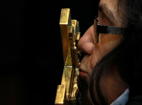 A woman kisses a cross during the Orthodox Christmas mass at St Kliment Orthodox church in Skopje