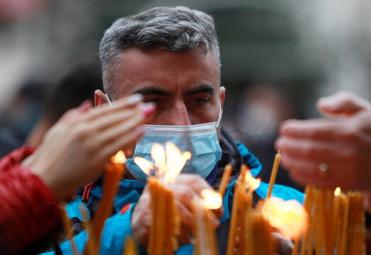 A believer wearing a protective face mask amid the coronavirus disease (COVID-19) outbreak attends a service on the Orthodox Christmas at the St. Klement Cathedral in Skopje