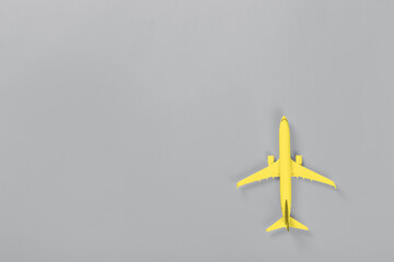 Yellow Model of passenger airplane on ultimate gray colored paper texture