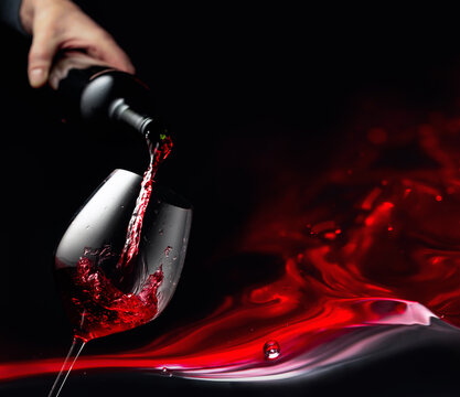 Pouring red wine in a glass goblet.
